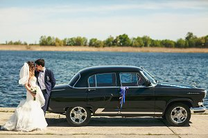 Newlyweds kiss leaning to an old car