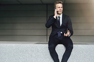 Discussing man wearing suit sits on brick