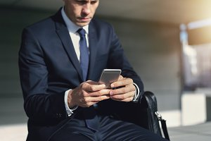 Young businessman sitting outside and using phone