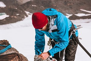 Man climber packing backpack