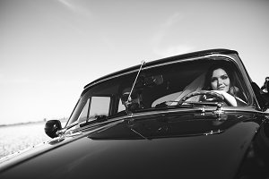 Smiling newlyweds sit in an old car