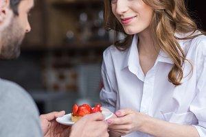 Happy couple with strawberry cake