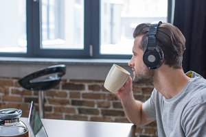 Man using laptop and drinking coffee