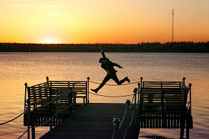 Happy man jumps up on the bridge