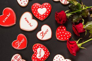 Beautiful gingerbread heart and red roses on a black background. Postcard for Valentine's day, March 8, mother's day or Wedding.
