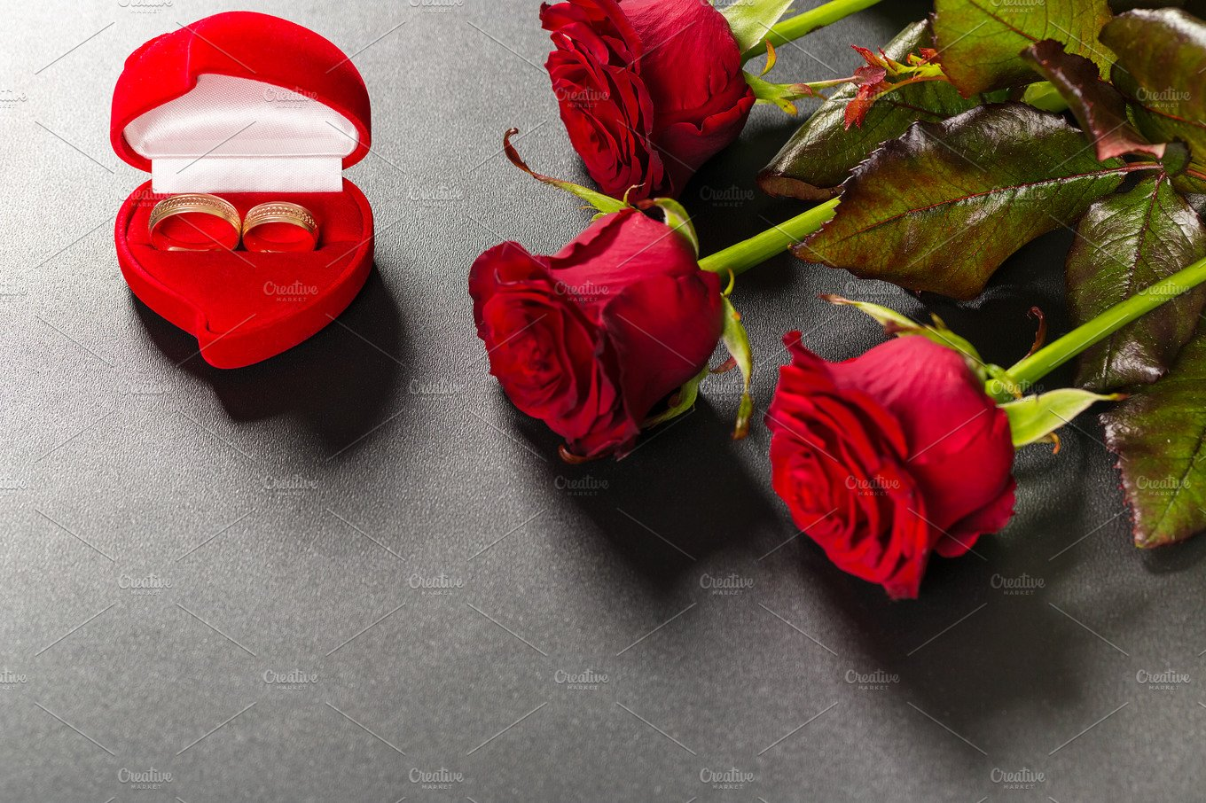 Beautiful red roses bouquet and wedding rings on a black background ...