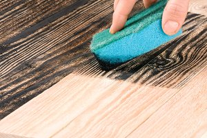 painting wooden board with a sponge in black color