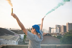 Male teenager holding colorful smoke sticks up in the air over urban city background