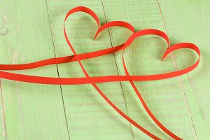 Two hearts made of red paper ribbon isolated on white background