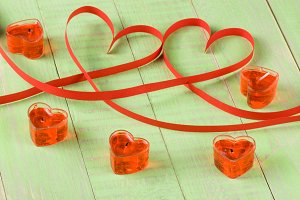 Two hearts made of red paper ribbon with candles isolated on white background