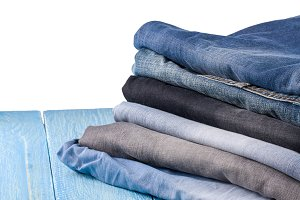 stack of jeans on  blue wooden background