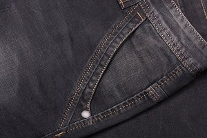 front pocket of dark jeans close up