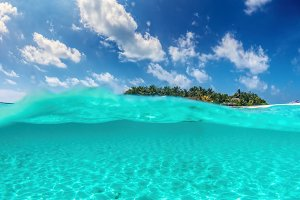 Tropical island on Indian Ocean, Maldives. Half underwater shot