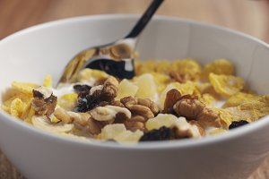 closeup eating with a spoon breakfast with corn flakes and mix of nuts and fruits
