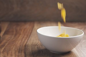 motion blurred corn flakes falling into white bowl on wooden table