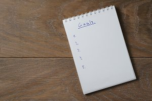 blank notepad on wooden table with word goals