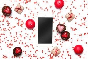 Flatlay with confetti, heart & phone