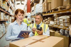 Warehouse managers looking at tablet pc