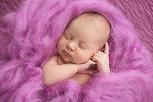 sleeping newborn girl on pink wool