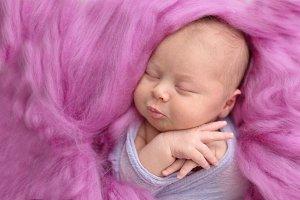 newborn girl sleep on pink wool