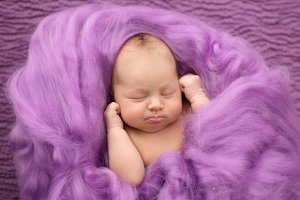 Newborn girl on pink background