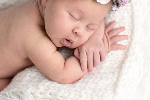 Newborn with wreath , close-up