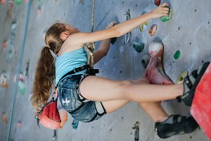 One teenager climbing a rock wall