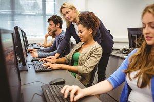 Attractive teacher helping her student in computer class