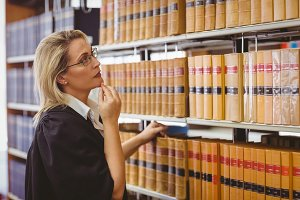 Lawyer wearing glasses and looking for a book in the shelf