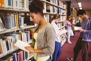 Students reading book against bookshelves