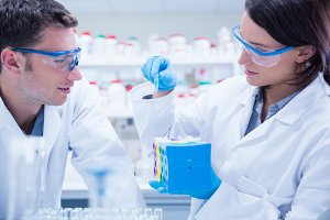 Two chemists wearing safety glasses and working together