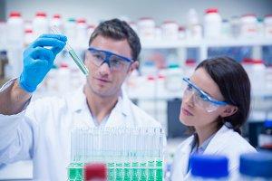 Smiling chemist holding test tube containing liquid