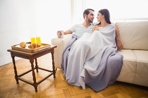 Cute couple relaxing on couch under blanket