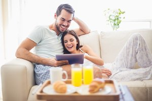 Cute couple relaxing on couch with tablet at breakfast