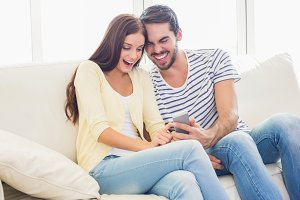 Cute couple relaxing on couch with smartphone