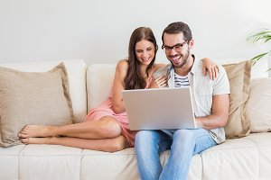 Hipster couple using laptop on couch
