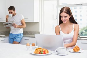 Young woman using laptop at breakfast