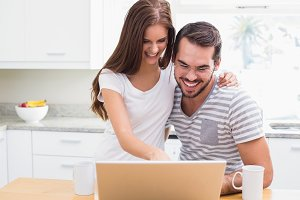 Young couple smiling and using laptop
