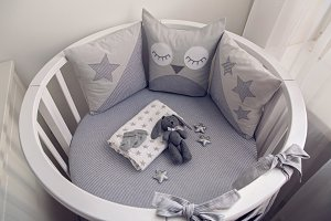 round white baby bed with gray pillows
