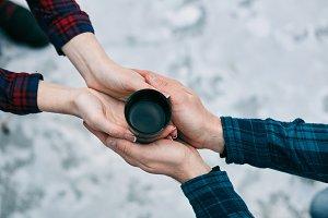 Top view cup of hot tea in lover's hands