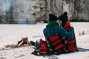 Couple sitting near a bonefire. They are covered with  warm blanket