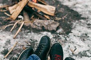 Guy and girl warm feet near a fire