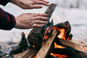 Girl warms hands near a fire in winter