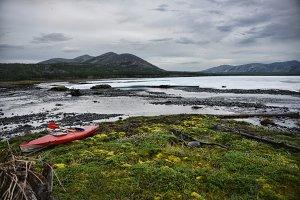 Kayak on the grass next to frazil