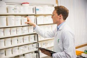 Handsome pharmacist taking medicine from shelf