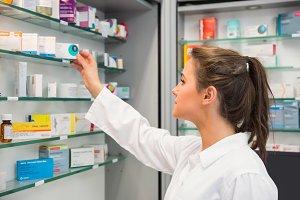 Junior pharmacist taking medicine from shelf