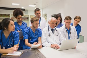 Medical students and professor using laptop