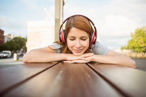 Woman lying on bench listening to music with eyes closed