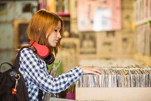 Pretty redhead searching a vinyl