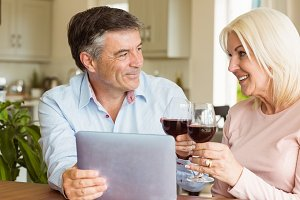 Happy mature couple using tablet drinking red wine